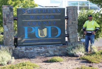 Erik Gardipee standing next to the Northern Wasco County PUD sign