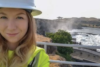 Cherish Southard, an electrical technician trainee at Northern Wasco County PUD, with the spillways on The Dalles Dam in the background.