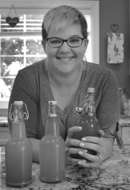Leslie Sullivan holding a bottle of kombucha