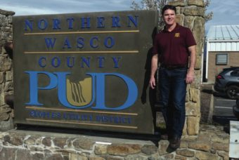Harvey Hall standing next to the Northern Wasco County PUD sign