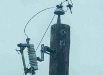 A fuse cutout attached to power pole.