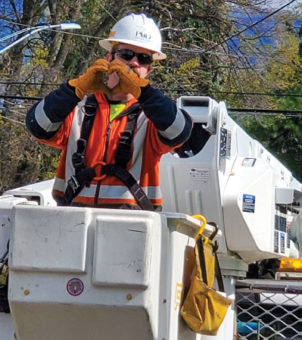 Journeyman lineman in a bucket truck, making a heart with his hands.