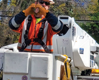 A lineman in his box truck, making a hand heart gesture