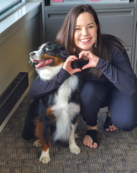 A young woman with her dog beside her, making a heart with her hands