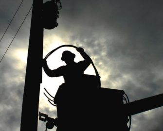 Outline of a lineworker working on a powerline