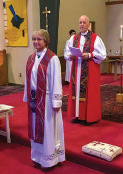 Marilyn standing in church wearing a vestment, with a bishop standing behind her